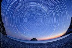 Star trails over the northern sky on a beach. by helensotiriadis | Stocksy United