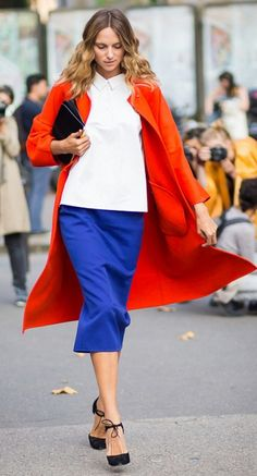 tomato-red coat layered over a crisp button-up and vibrant blue skirt