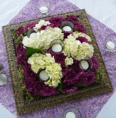 wedding centerpiece: DIY idea: square picture frame, spray glass with mirror spray, then put bouquet in vase surrounded by votives.