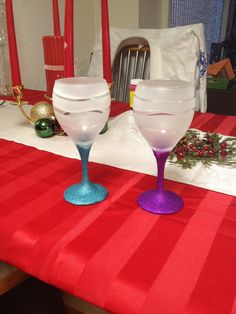 DIY wine glasses, dollar store wine glasses, modpodge bottom add glitter wait to dry modpodge over to keep glitter from flaking then put different size rubber bands around top and spray with frost paint. Remove rubber bands. Out comes these beautiful glasses.