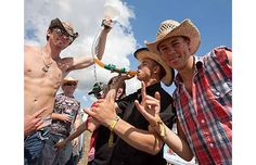 "From left, Landon Ruszkowski, from Edson, Alta. holds up ""Bettsie"" the beer bong for his friend DJ Talpash while he drinks with friend Tanner Paulhus from Edmonton on the camp grounds at the Big Valley Jamboree."