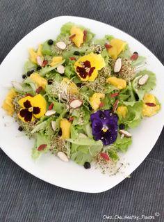 Insalata verde con fiori commestibili, mandorle, mirtilli, mango, bacche di goji e germogli di erba medica ----- Green salad with edible flowers, mango, almonds, blueberries, goji berries and alfalfa sprouts