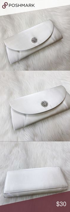 "NWT David's Bridal Ivory Clutch NWT. David's Bridal Ivory Clutch. So pretty! Silver jeweled hardware detail. Measures 10""x4"". The perfect bag for the beautiful ride. Also comes with a NWT David's Bridal garter [pictured]. David's Bridal Bags Clutches & Wristlets"