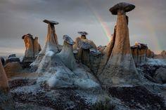 Hoodoos en desierto de Ah Shi Sle Pah. A primera vista puede parecer una colección de hongos, pero el arcoíris delata el tamaño de las formaciones. Llamadas 'Hoodoos', estas altas y puntiagudas rocas se forman en desiertos áridos. La piedra que se balancea en lo alto es mucho más dura que el resto y sirve para proteger la columna de los elementos de la naturaleza.