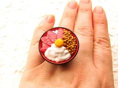 "This is soooo cute! This is a bowl of rice and on top are 4 toppings-""maguro"" (tuna), ""natto"" (fermented soy beans), ""yamaimo"" (mountain potato) and an egg.   It is on a silver tone adjustable band that will fit most ring sizes. It measures about 3.2 cm wide 2.2 cm high tall.   SouZouCreations' products are made with attention to detail, creativity and long lasting dependability."