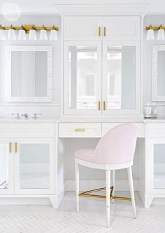 Corea Sotropa Interior Design - Feminine bathroom mirrored cabinets adorned with brushed brass pulls opening to a concealed make up vanity paired with a pink upholstered stool placed atop a marble herringbone floor.