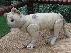 Antique Margarete Steiff Cat 1903-1904. Was once made of the highest quality mohair but it has none left and only the burlap remains. Shoe button eyes. Body filled with wood fibers. It has discs to make its legs move.