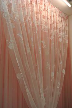 Tendaggio in velo color rosa con tenda superiore trasparente con cascata di fiori.
