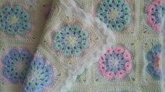 African flower hexagon blanket in soft pastel colours.