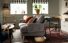 A multi-purpose living room with a desk, sofa, and other furniture..
