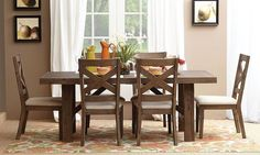 Hampton 5-piece dining set includes solid acacia trestle table in sandblasted light cocoa brown and four X-back side chairs with cream colored seat cushions.