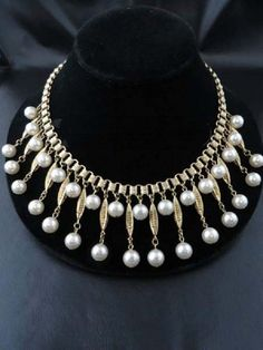 Offered is this lovely bib necklace marked Coro in script. This is such a flatterling style - faux pearls dangling from long ornate finials on a