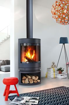 The super efficient award winning Emotion fireplace by Skantherm adapts to any space with is optional wood storage compartment and Thermostone heat bank.