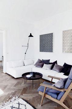 Mig & min bolig: Hanne Berzant, ejer af By Nord Copenhagen - Boligliv Sofaen er fra Saxo Living, sofabordet er 'Bowl Table' fra Mater, og lampen er designet af Serge Mouille. Wegner lænestolen er et af Hannes yndlingsmøbler og et arvestykke fra bedsteforældrene. Puderne er fra By Nord, og kunstværkerne over sofaen er fra en japansk samarbejdspartner.
