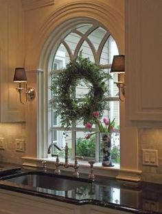 An unexpected warm touch by placing sconces on either side of the window over the kitchen sink by Laura L