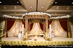 An Indian bride and groom wed in a traditional Hindu ceremony. They choose a classic theme of ivory, red, and gold for their wedding and a soft green and violet theme for their reception.