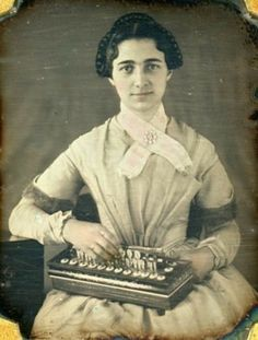 She's adorable and she plays the flutina! 1840s (She also is wearing a ring on her forefinger.)