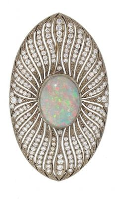 Antique Edwardian Opal and Diamond Brooch in 18K. Romantic yet strong, this antique Edwardian opal and diamond brooch is a dreamy design. A central bezel set opal, flashing with red, green and blue, is framed by smooth waves of pave set diamonds that shimmer around the entirety of this oval shaped brooch. Circa 1905.