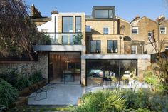 The Coach House is a slender three-storey building that steps down towards the rear, opening up into an L-shaped living area that overlooks a garden.