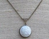 This beautiful necklace can be found on etsy.  It is an antique brass/gold locket with a vintage milk glass floral button added to it.