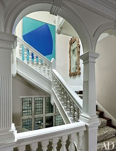 On the staircase, a Leon Polk Smith painting is displayed near a George I–style gilded mirror   archdigest.com