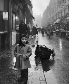 A young Jewish girl stands in a rainy street in Whitechapel in April 1954. Too young to understand the full horrors of the Holocaust, which may have brought her family to Britain a few years earlier, she goes about her daily life