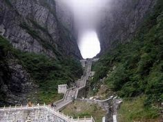 """Heaven's Gate, Zhangjiajie City, China. It's about a 7 mile hike/climb. For those of you who aren't afraid of heights, there is a cable car ride that is the longest in the world at 7455m long and 1279m high. Once you arrive, you still have to climb the final steps to get to """"Heaven's Gate."""" At the top is a 500 year old Temple."""
