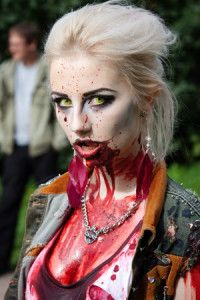 Woman dressed as a zombie, with blood oozing out of her mouth and onto her hip clothing