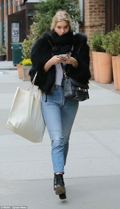 Low-key look: The 26-year-old styled up her attire with black boots and a grey satchel, wh...