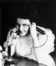 Woman using a 1900s candlestick phone
