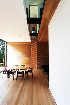 A textured wood walls meets a glass cutaway on the second floor. The Wishbone chairs are by Hans Wegner.