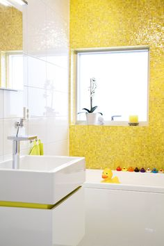 Yellow tile, rubber duckies, modern sink. Fun bathroom for a kid OR adult.