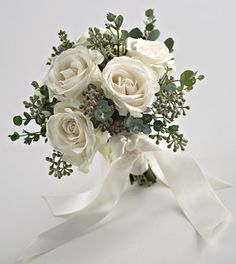 White roses accented with a couple different styles of Eucalyptus. This size would be good for a bridesmaid. It seems a little small for a bridal bouquet, but if you like the small bouquet look it could be for you. $56