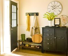 This entryway is filled with smart storage solutions to make the most of limited space. Next to the door, a shoe rack offers space to place shoes upon entering the home. Next to the rack, an antique cabinet provides a spot to set keys and mail, while the doors and drawers conceal items such as bags and umbrellas.