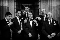 Black & white photo of the groomsmen enjoying their gift and smoking the cigars during the wedding reception.