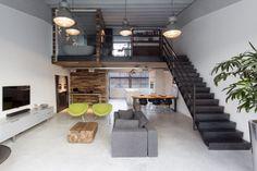 Woonkamer inspiratie in loft met donkere trap en design meubelen