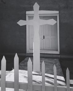 1961 Cross and Church, Canoncito, New Mexico [picket fence and cross painted white, centered on white door in adobe church] By Ansel Adams 92.3.45