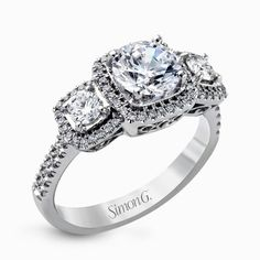Three stone engagement rings are so glamorous, but three halos? That's just exquisite! We're obsessed with this ring by Simon G Jewelry