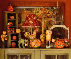 Vintage pumpkin decorations: Rare 1940s jack-o'-lanterns flank The Sheepish Boy, a one-of-a-kind reproduction of a pumpkin-headed lad carrying a pumpkin basket. In back, a vintage Fairy Seed Company poster coordinates with the rich orange wall when the Halloween decorations are gone.
