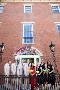 The bridal party and groomsmen pose by the historic brick wedding venue for this outdoor wedding day.