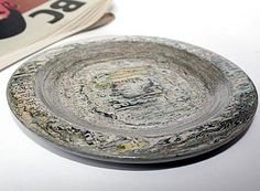 A decorative interior bowl produced from expired newspapers.    Each page is layered together and compressed into a block, once dried it is then turned on a wood lathe.        A vanish coating is then added to protect the paper and enhance the colours and words appearing in the surface patternation.    The piece is approximately 1.5cm in height and 20cm in diameter    Online Cost = $149