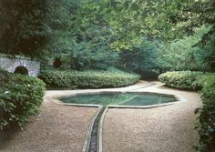 A gently curving rill & octagonal pool, surrounded by a decomposed granite pathway in a bowl of dense green planting at Rousham House in Oxfordshire, England. Designed by William Kent in the mid-18th century (a further development of Charles Bridgeman's plan)