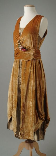Evening Dress: 1921, velvet bodice, and front panels of lamé, overall skirt is caught up at the sides with velvet cording and bullion tassels to create an eighteenth century effect, includes a small accent of metallic flowers at the waist.