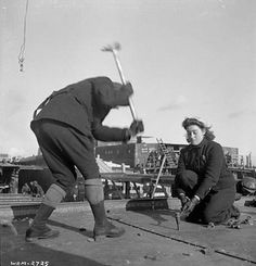 Female shipyard worker swings a heavy hammer to drive a rivet into place while another female shipyard worker holds the rivet in place during construction of a ship in the Pictou shipyard, Nova Scotia, January 1943.