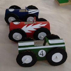 Racing cars. Toilet paper rolls painted. Paint circles of cardboard and stick smaller circles of paper inside them. Slit top to make seat and fold back. Add decorations and racing numbers with paper and glue. Stick wheels on with string. Now for the racetrack.