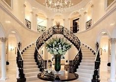 A spacious foyer with a domed ceiling and double staircase makes a grand entranc. A spacious foyer with a domed ceiling and double staircase makes a grand entrance to this home. An elegant chandelier and black and white staircase co. White Staircase, Double Staircase, Grand Staircase, Staircase Design, Chandelier Staircase, Luxury Staircase, Staircase Ideas, Open Stairs, Spiral Staircases