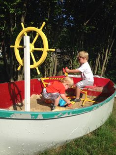 Paint and a ships wheel turned this dingy into an awesome sandbox!