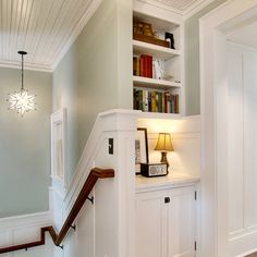 Yep, love everything about this hallway/stairway - woodwork, built-ins, light fixture, colors... all charming and perfect.
