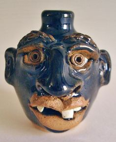 "This is a miniature, grotesque face jug.  It is marked ""North Cole Pottery"" and measures 2 & 1/2"" high. Although it looks blue, the color is the typical ""root beer brown""."