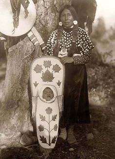 (First baby carrier) Flathead Indian Mother. Photo was made in 1910 by Edward S. Curtis. The photo documents Flathead woman standing by tree holding baby in cradleboard in front of her.